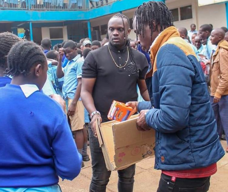 DJ Kriss Darlin distributes sanitary towels at Olympic Primary School in Kibra. PHOTO | COURTESY